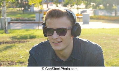 Young man with headphones at green grass - Handsome young...