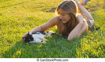 Happy cute girl playing with adorable cats - Woman petting...