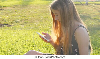 Young woman on grass with phone