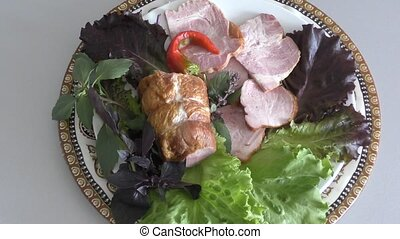 Assorted meat with fresh Greens on the table on the dining...