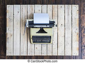Retro typewriter over vintage wooden background