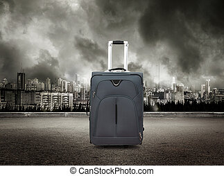 Suitcase on view of city in stormy sky background