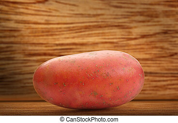One fresh whole potato on wooden background