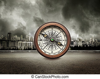 Compass on view of city in stormy sky background