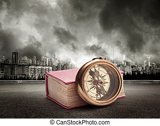 Book and compass on view of city in stormy sky background