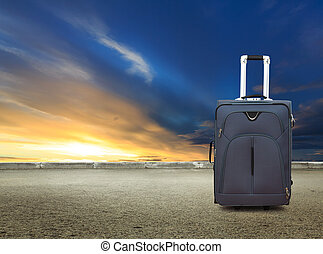 Suitcase at sunset sky and road background