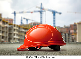 Red helmet on buildings and cranes background