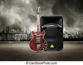 Guitar and column speaker on view of city in stormy sky...