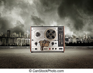 Old reel tape recorder on view of city in stormy sky...