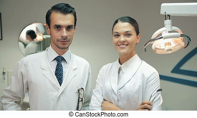 Dentists look at camera at office
