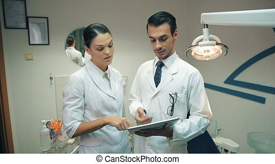 Team of dentists at working at office - Male and female...