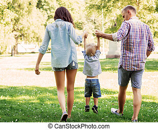 Mother and father walking on fresh air with their son -...