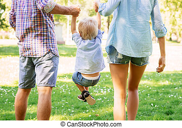 Young couple lifting their son while walking in the park