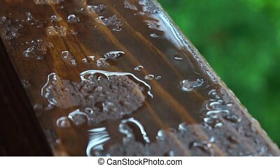 Rain drops on a wooden window sill like liquid metal or...