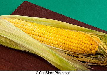 Corncob cooked corn lies on cutting board