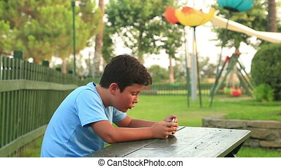 Young boy using mobil phone outdoor - Child relaxing with...