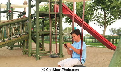 Child relaxing with smartphone in playground - Young boy...