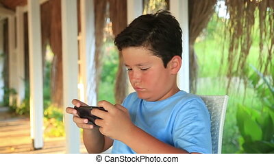 Child relaxing with smartphone - Young boy using mobil phone...