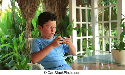 Child relaxing with smartphone in summer cafe - Little boy...