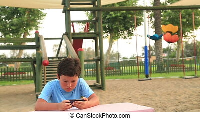 Child relaxing with smartphone in playground