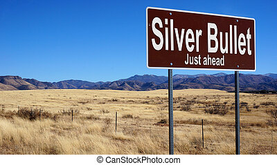 Silver Bullet brown road sign with blue sky and wilderness