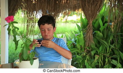 Child relaxing with smartphone in summer cafe - Young boy...