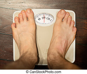Man standing on scales in bathroom. About 100 kg.