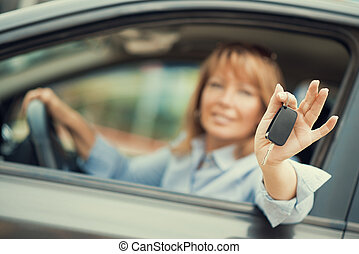 Woman buying a car - Woman sitting in a car and showing car...
