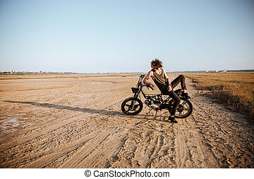 Young brutal man laying on his motorcycle and posing