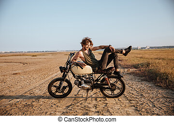 Young brutal man laying on his motorcycle and posing - Young...