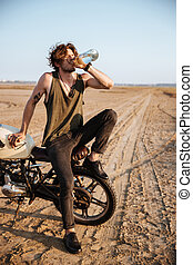 Young brutal man sitting on his motorcycle and drinking...