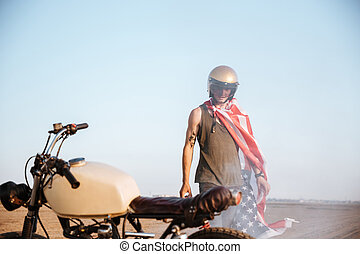 Close up of motorcycle with a man on the backgroud standing...