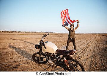 Man in golden helmet waving american flag at the desert
