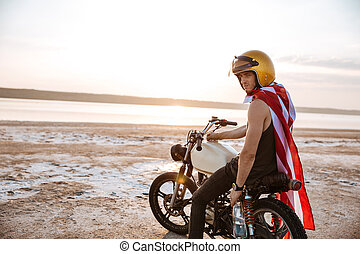Man in golden in american cape sitting on his motocycle -...
