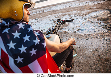 Close up portrait of man wearing helmet and american flag -...