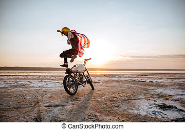 Brutal man jumping over his motorcycle at the sunset in...