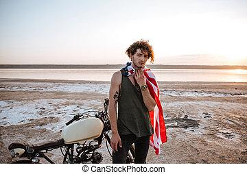 Man wearing american flag cape and golden helmet posing -...
