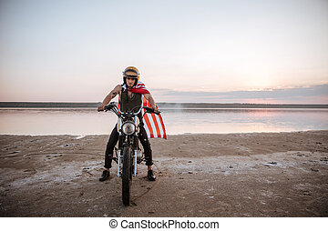 Man in golden helmet and american flag cape driving...