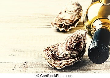 Fresh oysters with white wine bottle. Food background with...