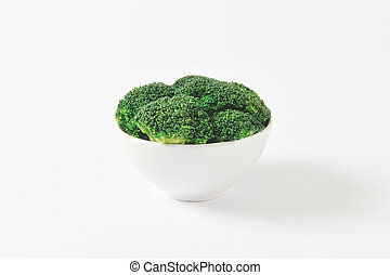 Raw broccoli florets in white bowl