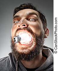 Caucasian man with bulb in his mouth on gray background -...