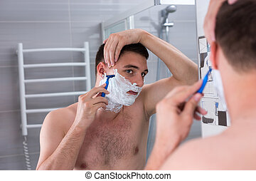 Handsome young man shaving his face with a razer and looking...