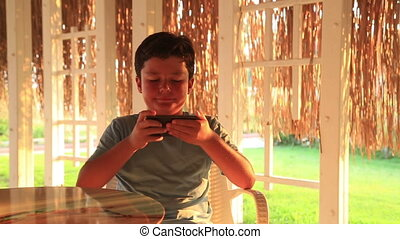 Young boy with smartphone in summer cafe - Little boy gaming...