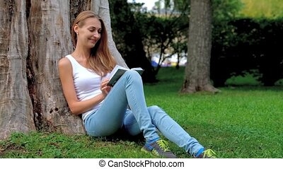 Young woman reading a book in the park and dreaming