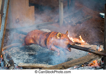 Delicious vegitarian hell - A pig is roasted on an open...