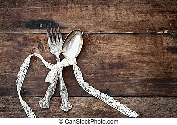 Antique Silverware over a Rough Wooden Background