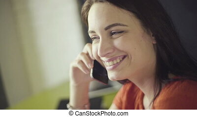 Portrait of attractive brunette woman talking on mobile phone at home