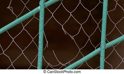 torn white grid on the fence slow motion video - closeup of...