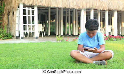 Young boy play smartphone on the grass