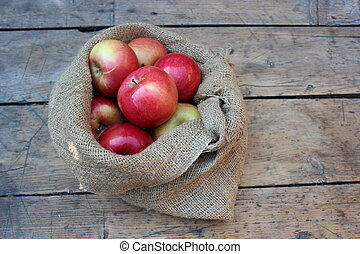 Apples in a bag lying on wooden boards